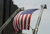 An Large American Flag hanging between Firefighter Truck Ladders — Stock Photo