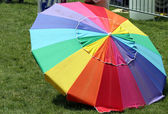 A Rainbow-Colored Parasol on green grass during Indy Pride — Stock Photo