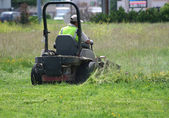 Man mowing lawn with a ride on lawn mower — Stock Photo