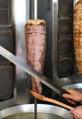 Koken snijden turkse lam döner kebab met een scherp zwaard zoals mes — Stockfoto