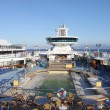 Typical Cruise ship deck with swimming pool,sunbeds and bar. — Stock Photo #34804101