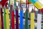 Bunte zaun wachsmalstift-förmigen säulen aus — Stockfoto