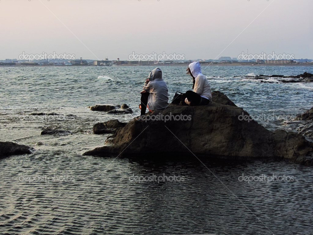 Two girls sitting on a cliff, looking at the ocean  Stock Photo #15349609
