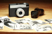 Old camera next to out of focus black and white photographs — Stock Photo