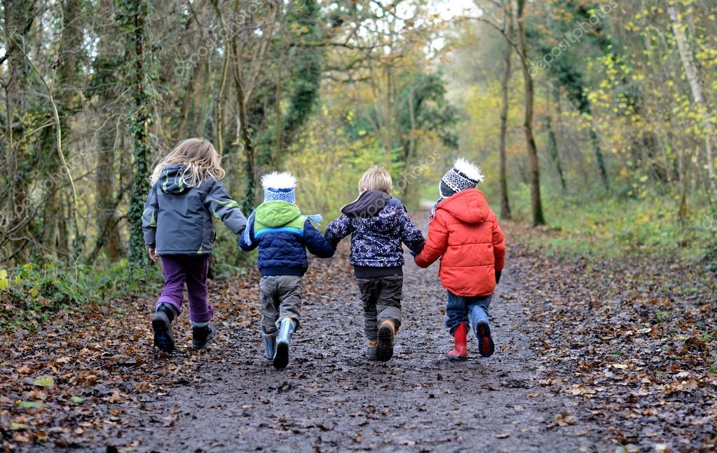 Four children holding hands walking down a wooded path having fun — Stock Photo #16792505