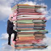 Businessman climbing pile of endless paperwork — Stock Photo