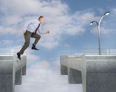 Businessman jumping gap on bridge — Stock Photo