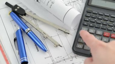 Pricing an architectural drawing blueprint with dividers  and calculator. Hand typing number into calculator.