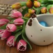 Laying easter eggs in chicken cup with bunch of pink tulips. In background a box of quail eggs. — Stock Video