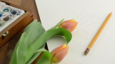 Preparación para pintar un tulipán en acuarela acuarela. abriendo una caja de acuarela y poniendo pincel sobre papel — Vídeo de stock