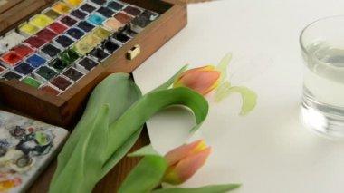 Ainting s štětec oranžový tulipán pupenu v vodovky a čisticí kartáč ve sklenici vody. — Stock video