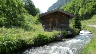 Hikers passing by a little alpine Hovel at stream water at Zillertal — Stock Video
