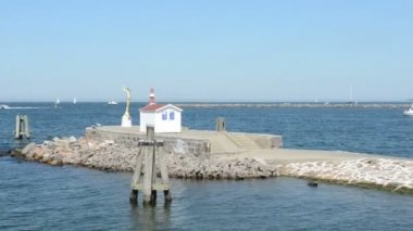 Small hut with a statue and alighthouse. The harbor entrance from Warnemunde in the Baltic Sea. — Stock Video