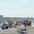 Stock Video: People on beach in Warnemuende on Baltic Sea. Small beach tents standing on sand. Located at Warnemuende on August 02, 2013