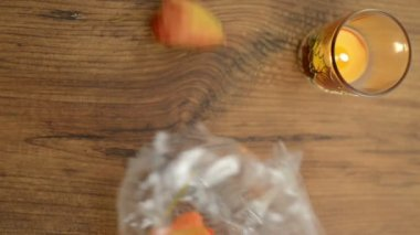 Tea light and bladder cherry decoration be tilted from a bag on the table. — Stock Video