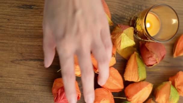La decoración de otoño como té luz y vejiga cerezo sobre una mesa de clasificación. — Vídeo de stock