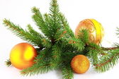 Branch of a New Year's fir-tree with gold ornaments. — Stock Photo