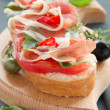 Bruschettwith prosciutto, tomato and basil. — Stock Photo #30248427