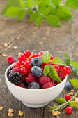 Assorted berries on wooden background (strawberries, raspberries, blackberries, blueberries) — Stock Photo
