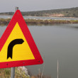 Traffic sign pointing right towards a water canal — Stock Photo #13130127