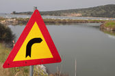 Traffic sign pointing right towards a water canal — Stock Photo