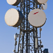 Communication tower with parabolic antennas - Stock Photo