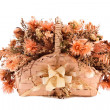 Decorative traditional wick basket with fake flowers in it — стоковое фото #13347309
