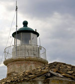 Lighthouse situated on top of an old building — Stock Photo