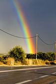 Rainbow over the highway after a heavy storm — Stock Photo