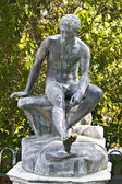 Ancient greek statue in middle of a garden — Stock Photo