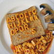 Alphabet written on toast - Stock Photo