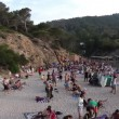 Stock Video: Crowds gather on famous benirras beach in ibiza