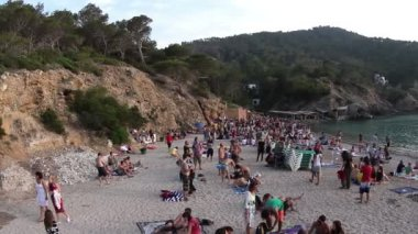 Crowds gather on the famous benirras beach in ibiza as sunset starts. this beach is famous for drummers playing together as the sun sets.