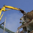 A crane breaking down a building, looking a bit like like a dinosaur eating! — Stock Video