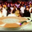 Dj record turntable with blurred dance crowd in background — Stock Video