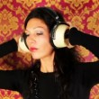 Stock Video: A sexy woman dances with retro white headphones