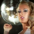 Sexy professional gogo lily malibu shot dancing and next to a large spinning discoball - Stock Photo