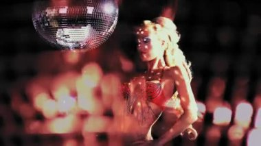 Sexy professional gogo lily malibu shot dancing and next to a large spinning discoball — Stock Video