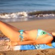 Beautiful girl sunbaths on the beach in a bikini at sunrise — 图库视频影像