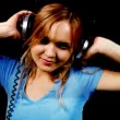Beautiful young blond woman dances in tight top and headphones - Stock Photo