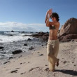 Young woman practices yoga on a beach at sunrise — Stockvideo