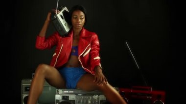 Sexy young woman sits ontop of a retro ghettoblaster listening to music — Stock Video