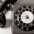 Close up of a hand ringing a number on an old fashioned telephone - 