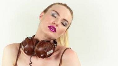 A sexy gogo dancer sitting and posing with headphones — Stock Video