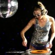 Stock Video: Sexy female dj dancing and playing records with disco style background