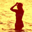 Woman dances alone in the sea at sunset — Stockvideo