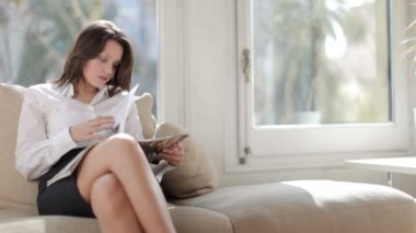 A pretty businesswoman reads, relaxing, or awaiting an interview — Stock Video