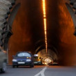 Cars entering and leaving a tunnel in rushhour - Stock Photo