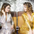 Stock Photo: Beautiful disco twins i golden and silver catsuit