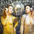Two beautiful sexy disco women in gold and silver catsuits danci — Stock Photo #50238721